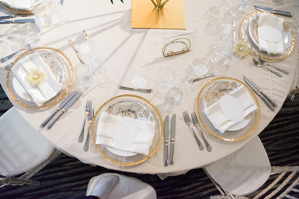 Downtown los angeles wedding shoot at the renaissance hotel table set up white table linen with white and gold place settings and white menu with wine glasses and white chairs