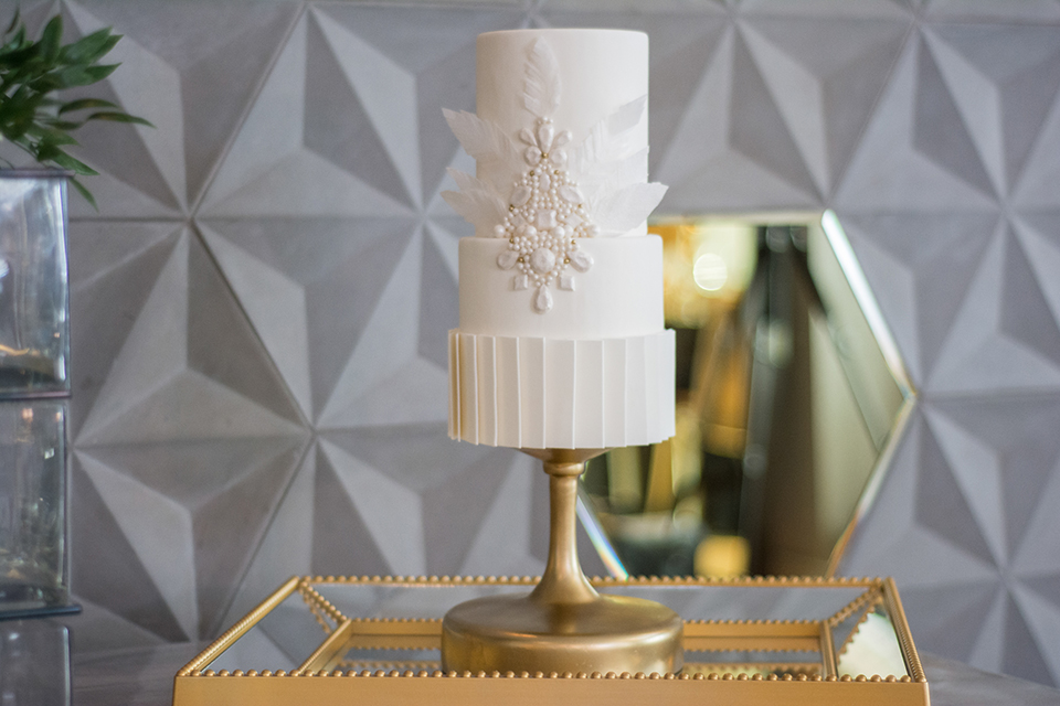 Downtown los angeles wedding shoot at the renaissance hotel wedding cake three tier white wedding cake with flower design on gold cake stand and gold table with grey background wedding photo idea for cake