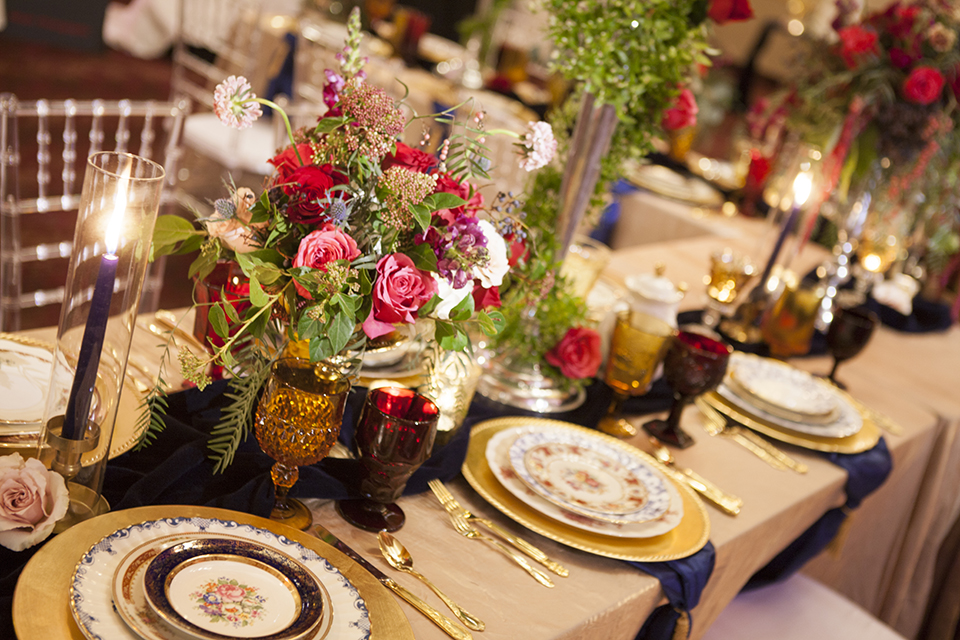 Beauty and the beast inspired wedding shoot at south coast winery table set up white table linen with navy blue table runner and white and gold place settings with pink and red flower centerpiece decor and tall candles with white and gold chairs