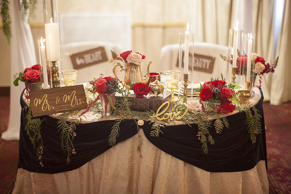 Beauty and the beast inspired wedding shoot at south coast winery table set up white table linen with navy blue table runner and white and gold place settings with pink and red flower centerpiece decor and tall candles with white and gold chairs sweetheart table