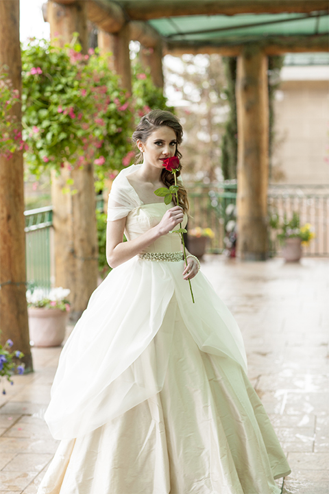 Beauty and the beast inspired wedding shoot at south coast winery bride ballgown with sheer illusion neckline and ruffled skirt with beaded belt and detail on bodice holding one red rose