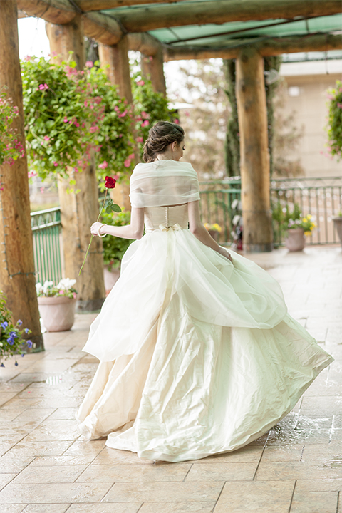 Beauty and the beast inspired wedding shoot at south coast winery bride ballgown with sheer illusion neckline and ruffled skirt with beaded belt and detail on bodice holding one red rose back of dress