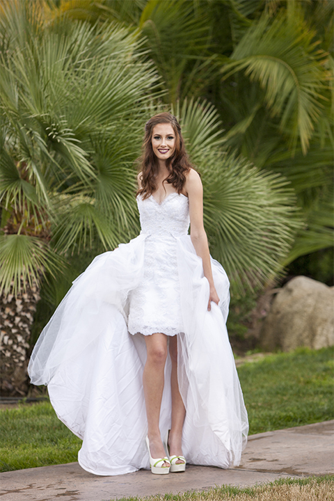 Beauty and the beast inspired wedding shoot at south coast winery bride strapless gown with ruffled skirt over short dress showing legs with lace design and sweetheart neckline holding dress