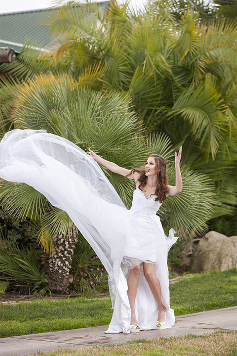 Beauty and the beast inspired wedding shoot at south coast winery bride strapless gown with ruffled skirt over short dress showing legs with lace design and sweetheart neckline twirling dress