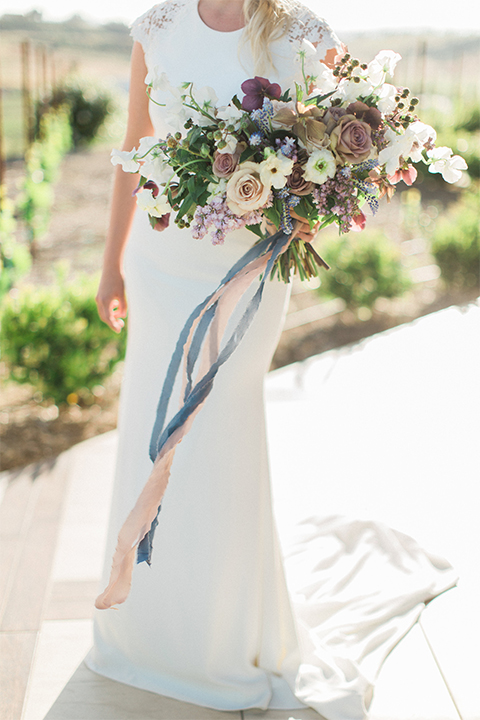 Temecula outdoor wedding shoot at avensole winery bride form fitting gown with lace detail on short sleeves and high neckline with hair in side braid holding white and green floral bridal bouquet with light blue ribbon decor close up