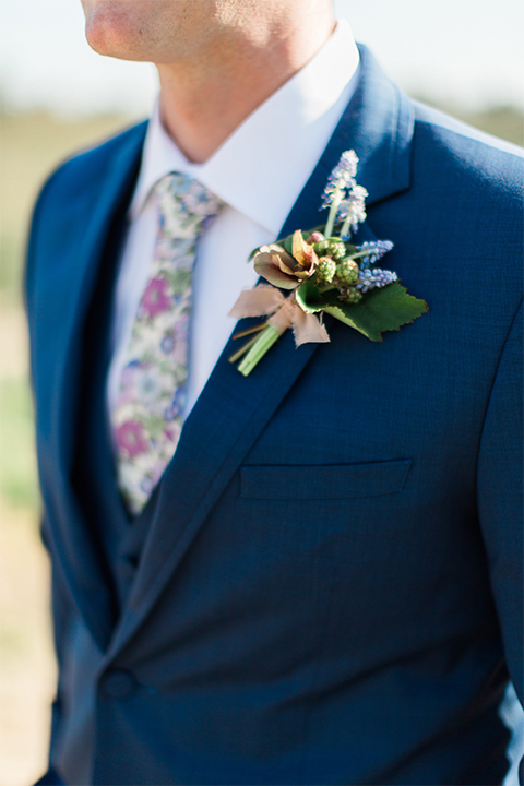 Temecula outdoor wedding shoot at avensole winery groom navy blue suit with matching vest and white dress shirt with long floral tie and green and blue floral boutonniere close up