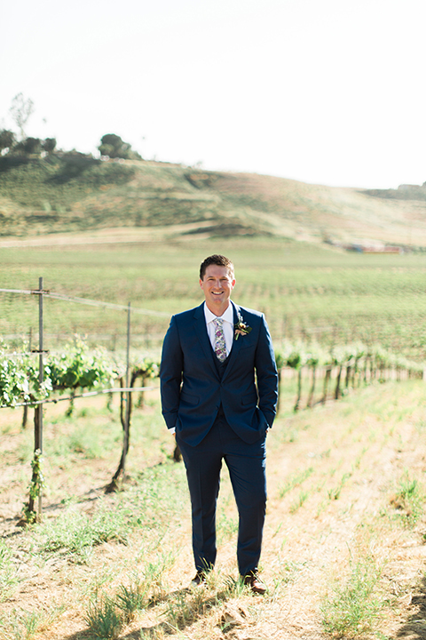 Temecula outdoor wedding shoot at avensole winery groom navy blue suit with matching vest and white dress shirt with long floral tie and green and blue floral boutonniere standing with hands in pockets