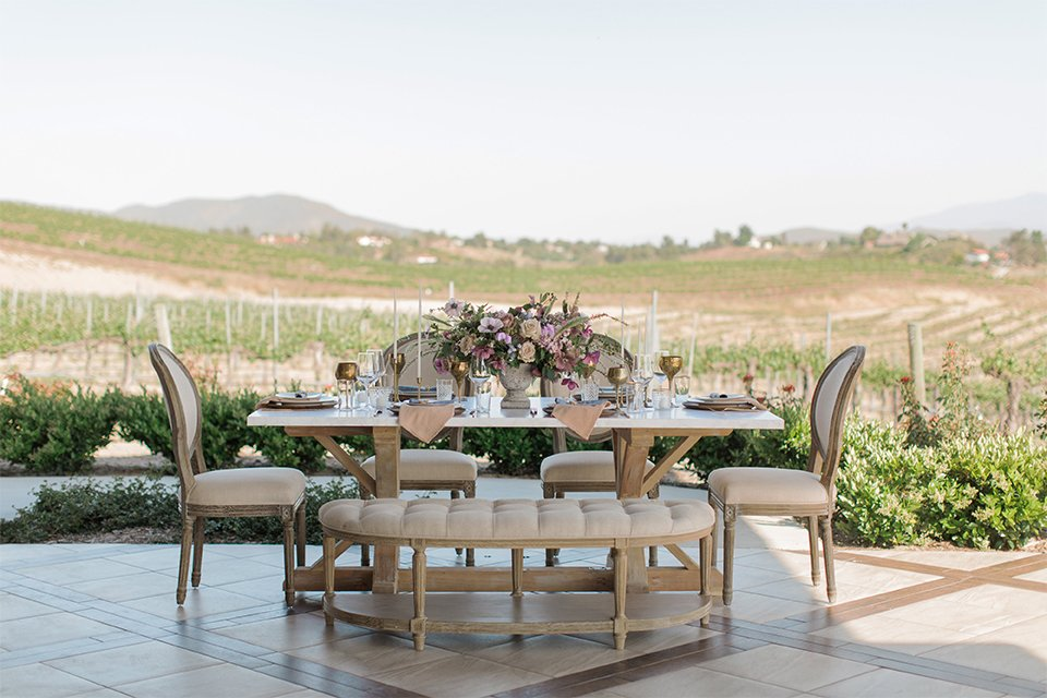 Temecula outdoor wedding shoot at avensole winery table set up light brown wood table with matching chairs and purple and green flower centerpiece decor with white place settings and blush napkin decor with gold wine glasses and white candle decor