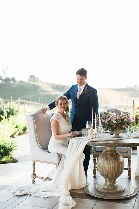 Temecula outdoor wedding shoot at avensole winery bride form fitting gown with lace detail on short sleeves and high neckline with hair in side braid with groom navy blue suit with matching vest and white dress shirt with long floral tie and green and blue floral boutonniere sitting at table