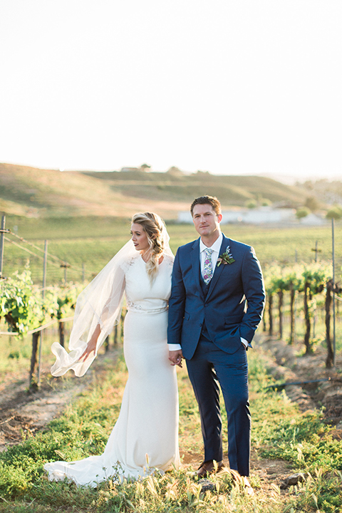 Temecula outdoor wedding shoot at avensole winery bride form fitting gown with lace detail on short sleeves and high neckline with hair in side braid with groom navy blue suit with matching vest and white dress shirt with long floral tie and green and blue floral boutonniere standing and holding hands