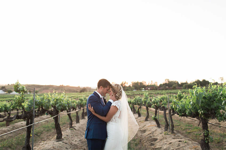 Temecula outdoor wedding shoot at avensole winery bride form fitting gown with lace detail on short sleeves and high neckline with hair in side braid with groom navy blue suit with matching vest and white dress shirt with long floral tie and green and blue floral boutonniere hugging