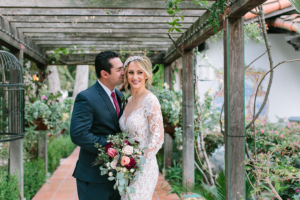 Orange county wedding shoot at rancho las lomas bride form fitting lace gown with lace long sleeves and sweetheart neckline with low illusion back with buttons and groom navy suit with matching vest and long burgundy tie with white floral boutonniere standing and hugging bride holding red and pink floral bridal bouquet