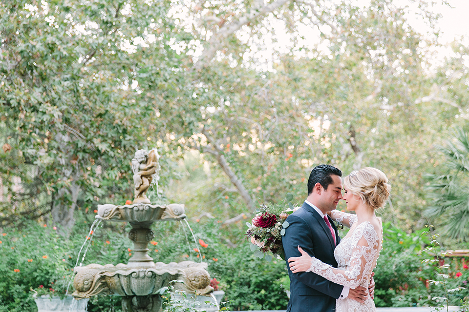 Orange county wedding shoot at rancho las lomas bride form fitting lace gown with lace long sleeves and sweetheart neckline with low illusion back with buttons and groom navy suit with matching vest and long burgundy tie with white floral boutonniere hugging by fountain and bride holding red and pink floral bridal bouquet