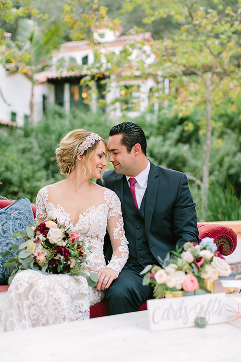 Orange county wedding shoot at rancho las lomas bride form fitting lace gown with lace long sleeves and sweetheart neckline with low illusion back with buttons and groom navy suit with matching vest and long burgundy tie with white floral boutonniere sitting on red vintage couch bride holding red and pink floral bridal bouquet