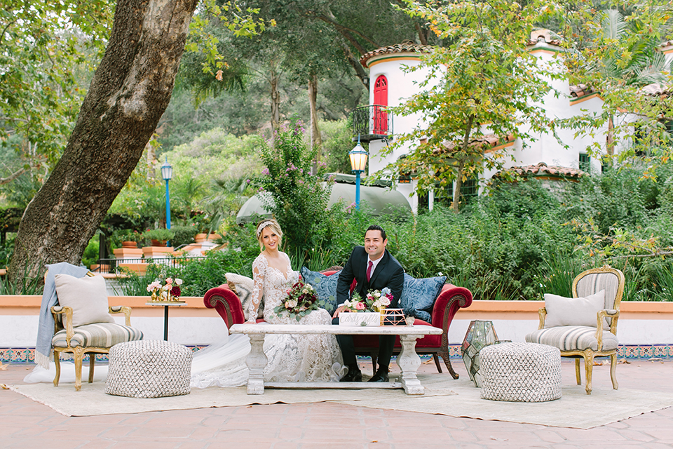 Orange county wedding shoot at rancho las lomas bride form fitting lace gown with lace long sleeves and sweetheart neckline with low illusion back with buttons and groom navy suit with matching vest and long burgundy tie with white floral boutonniere sitting on couch bride holding red and pink floral bridal bouquet