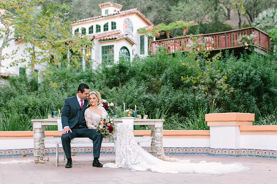 Orange county wedding shoot at rancho las lomas bride form fitting lace gown with lace long sleeves and sweetheart neckline with low illusion back with buttons and groom navy suit with matching vest and long burgundy tie with white floral boutonniere sitting at table bride holding red and pink floral bridal bouquet