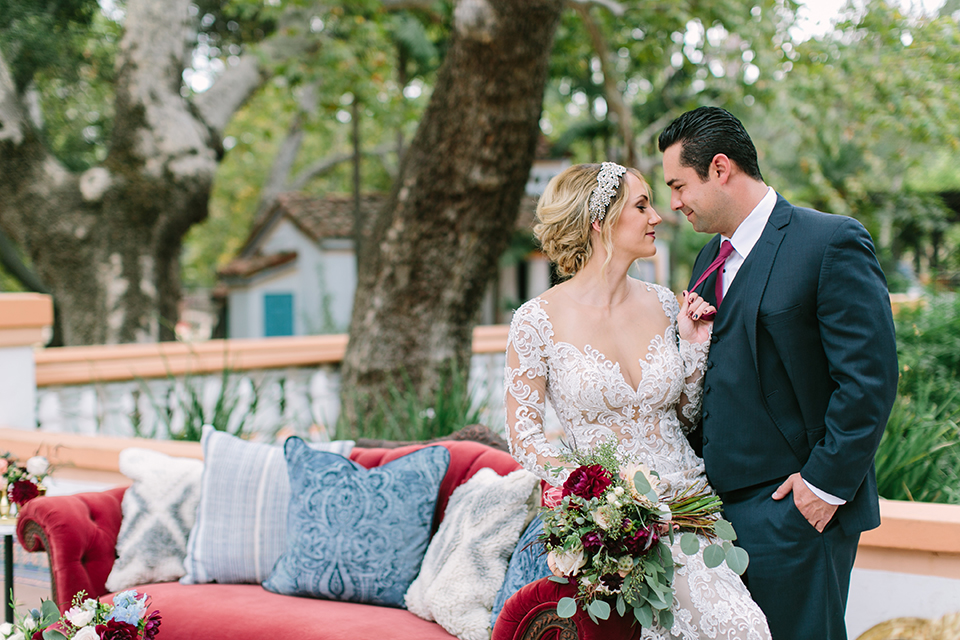 Orange county wedding shoot at rancho las lomas bride form fitting lace gown with lace long sleeves and sweetheart neckline with low illusion back with buttons and groom navy suit with matching vest and long burgundy tie with white floral boutonniere standing by lounge furniture bride holding red and pink floral bridal bouquet