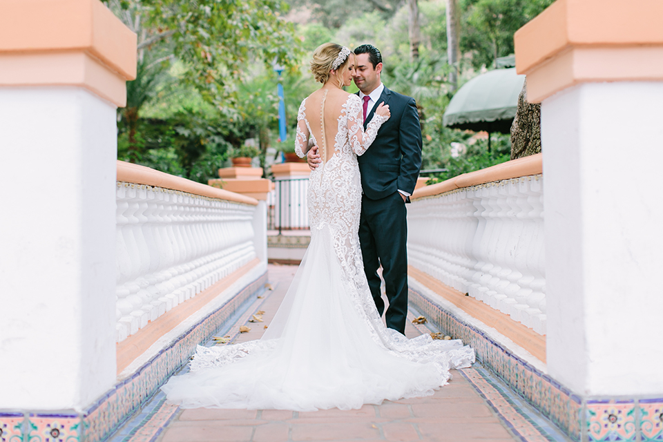 Orange county wedding shoot at rancho las lomas bride form fitting lace gown with lace long sleeves and sweetheart neckline with low illusion back with buttons and groom navy suit with matching vest and long burgundy tie with white floral boutonniere hugging