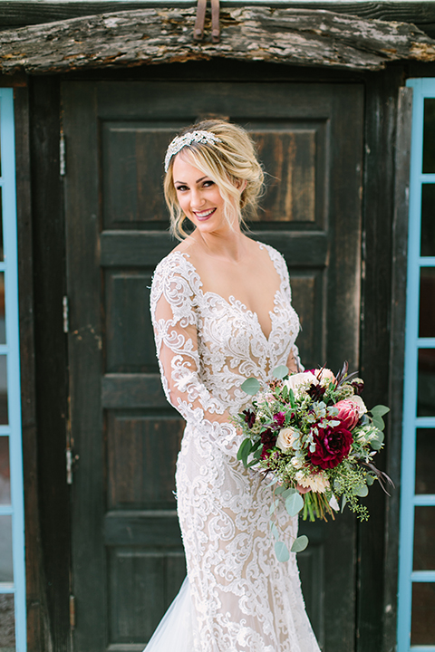 Orange county wedding shoot at rancho las lomas bride form fitting lace gown with lace long sleeves and sweetheart neckline with low illusion back with buttons holding red and green floral bridal bouquet