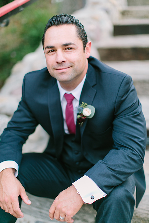 Orange county wedding shoot at rancho las lomas groom navy notch lapel suit with matching vest and white dress shirt with long burgundy tie and white floral boutonniere sitting