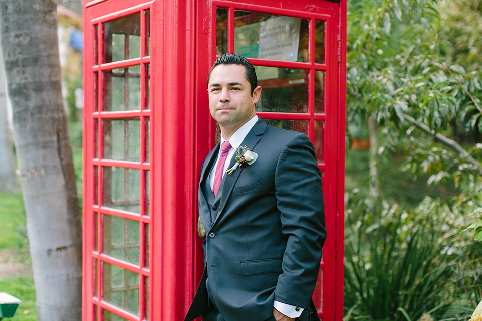 Orange county wedding shoot at rancho las lomas groom navy notch lapel suit with matching vest and white dress shirt with long burgundy tie and white floral boutonniere standing by red telephone booth