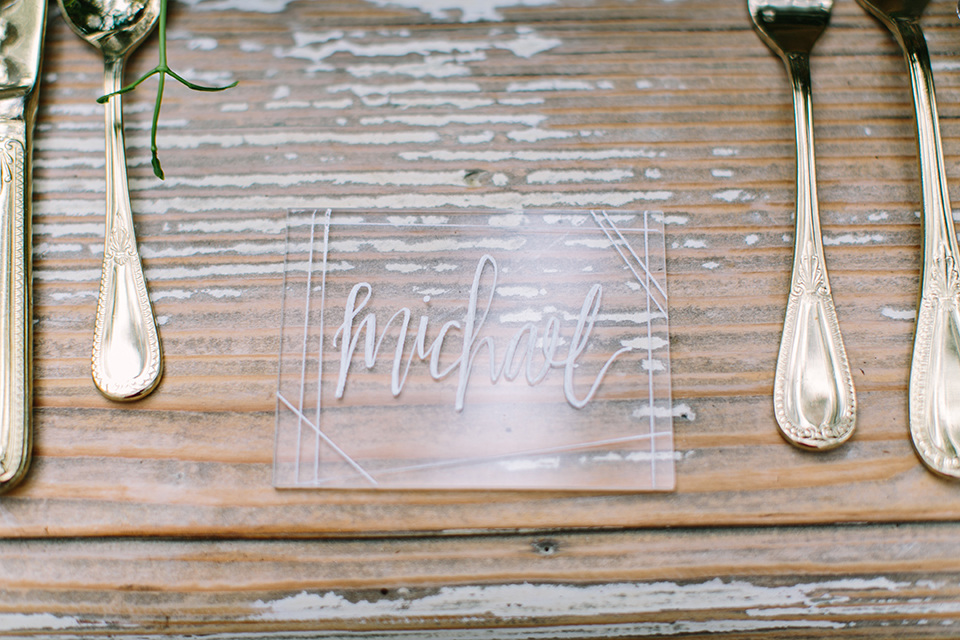 Orange county wedding shoot at rancho las lomas table set up light brown wood table with clear and blue place settings with silverware and red and green floral centerpiece decor with tall grey candles with clear calligraphy writing for name cards and white linen decor