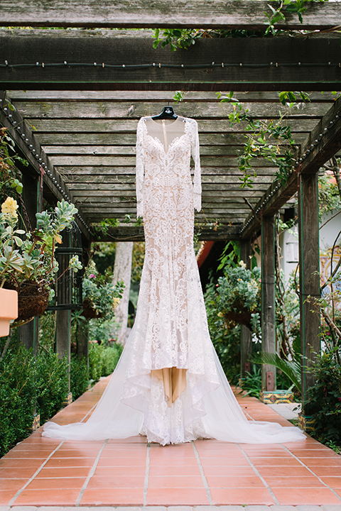 Orange county wedding shoot at rancho las lomas bride wedding dress hanging on hanger form fitting lace gown with long lace sleeves with illusion low back with buttons with greenery decor wedding photo idea for dress