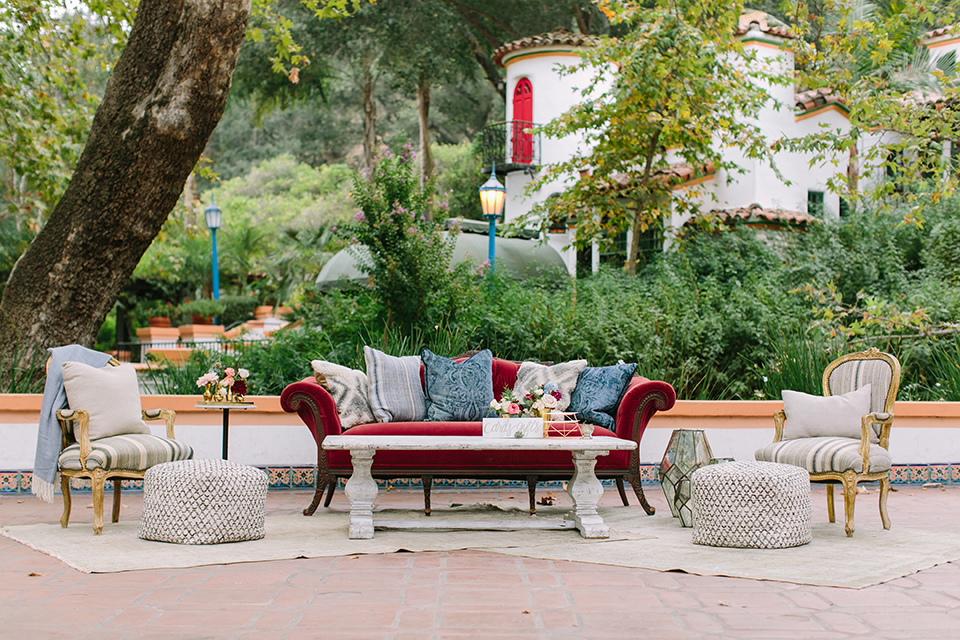 Orange county wedding shoot at rancho las lomas wedding lounge furniture red vintage couch with pillows and white chairs with table and white carpet with greenery decor and flowers wedding photo idea for lounge furniture cocktail hour
