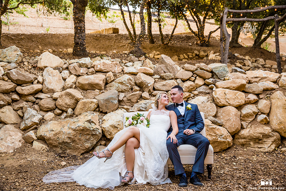 San bernadino outdoor rustic wedding at serendipity gardens bride a line chiffon gown with a high lace design neckline with a long veil and groom charcoal notch lapel suit with a matching vest and white dress shirt with a black bow tie and white floral boutonniere sitting on couch hugging