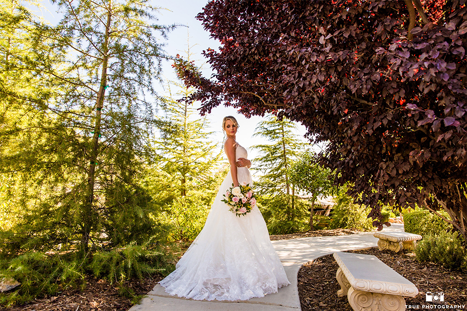 San bernadino outdoor rustic wedding at serendipity gardens bride a line chiffon gown with a high lace design neckline with a long veil holding white and green floral bridal bouquet