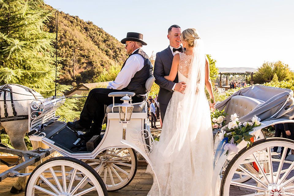 San bernadino outdoor rustic wedding at serendipity gardens bride a line chiffon gown with a high lace design neckline with a long veil and groom charcoal notch lapel suit with a matching vest and white dress shirt with a black bow tie and white floral boutonniere standing on carriage hugging and bride holding white and green floral bridal bouquet