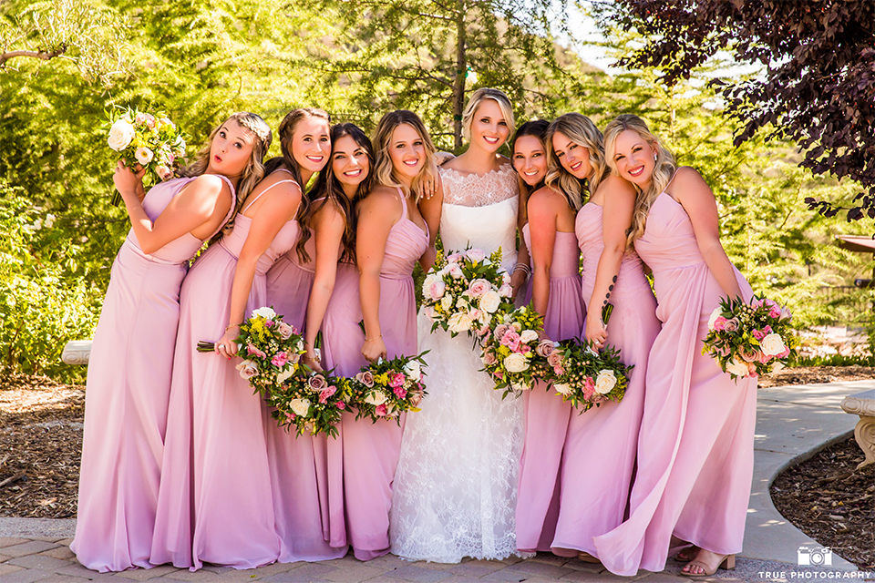San bernadino outdoor rustic wedding at serendipity gardens bride a line chiffon gown with a high lace design neckline with a long veil holding white and green floral bridal bouquet with bridesmaids long pink dresses and white and green floral bridal bouquets