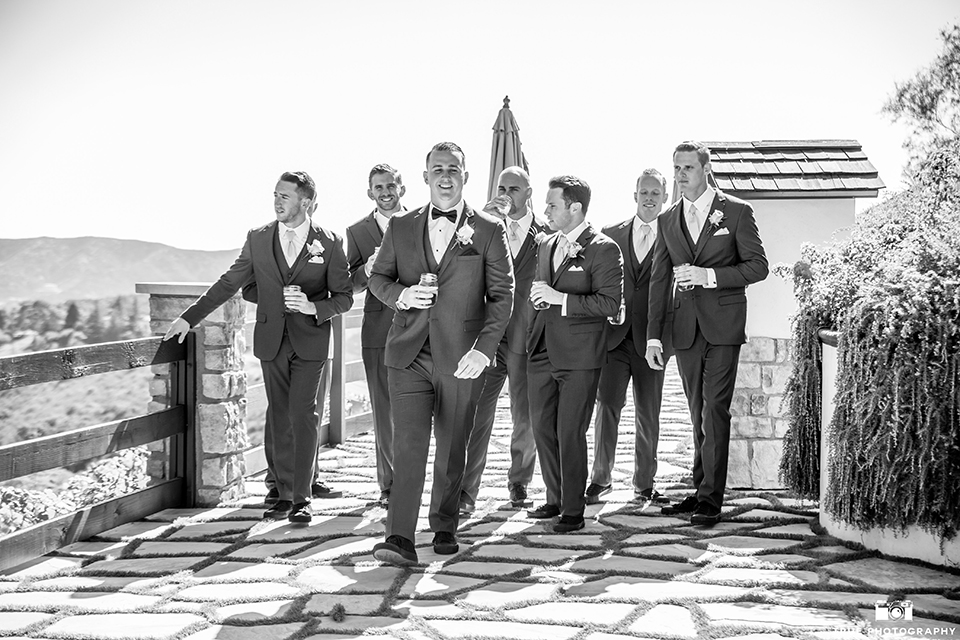 San bernadino outdoor rustic wedding at serendipity gardens groom charcoal notch lapel suit with a white dress shirt and a matching vest with a black bow tie walking with groomsmen charcoal grey suits with long ties black and white photo