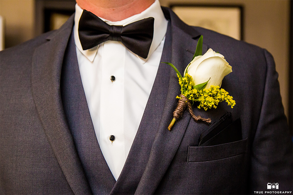 San bernadino outdoor summer wedding at serendipity gardens groom charcoal grey notch lapel suit with white dress shirt and black bow tie and white floral boutonniere close up