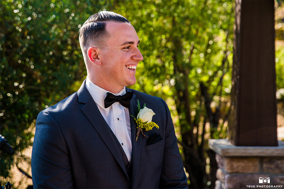 San bernadino outdoor summer wedding at serendipity gardens groom charcoal grey notch lapel suit with white dress shirt and black bow tie and white floral boutonniere watching bride walk down the aisle during ceremony