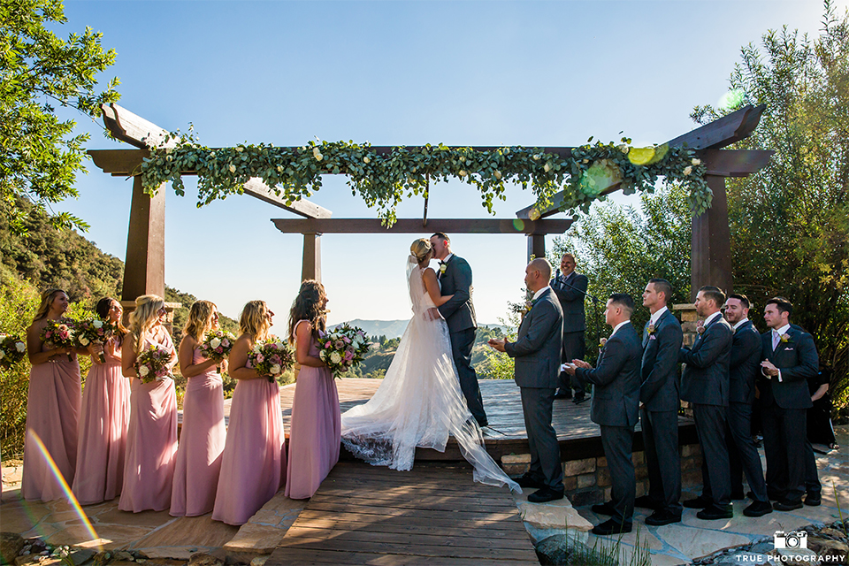 San bernadino outdoor rustic wedding at serendipity gardens bride a line chiffon gown with a high lace design neckline with a long veil and groom charcoal notch lapel suit with a matching vest and white dress shirt with a black bow tie and white floral boutonniere kissing during ceremony