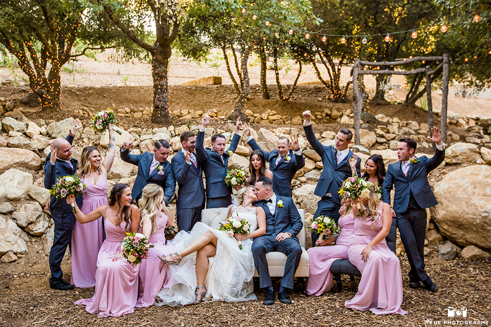 San bernadino outdoor rustic wedding at serendipity gardens bride a line chiffon gown with a high lace design neckline with a long veil and groom charcoal notch lapel suit with a matching vest and white dress shirt with a black bow tie and white floral boutonniere with wedding party bridesmaids long pink dresses and white and green bouquets with groomsmen charcoal grey suits with long ties