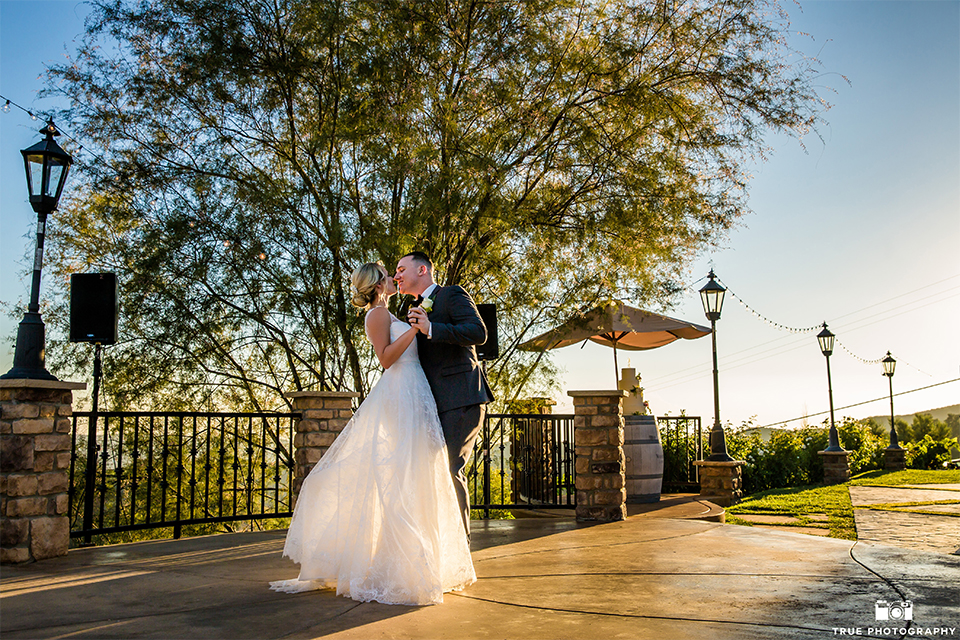 San bernadino outdoor rustic wedding at serendipity gardens bride a line chiffon gown with a high lace design neckline with a long veil and groom charcoal notch lapel suit with a matching vest and white dress shirt with a black bow tie and white floral boutonniere first dnce