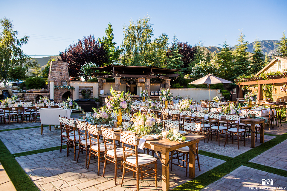 San bernadino outdoor summer wedding at serendipity gardens reception table set up with white table linens and brown wood tables and matching chairs and white and gold place settings with white and green flower centerpiece decor with gold vase and decor