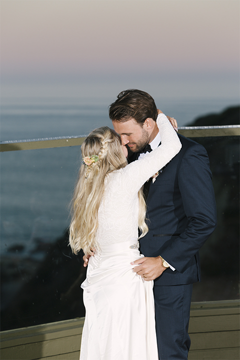 Dana point outdoor beach wedding at cannons seafood grill bride simple high neckline gown with long sleeves and a crystal belt with groom navy blue shawl lapel tuxedo with white dress shirt and black bow tie with white floral boutonniere first dance and hugging
