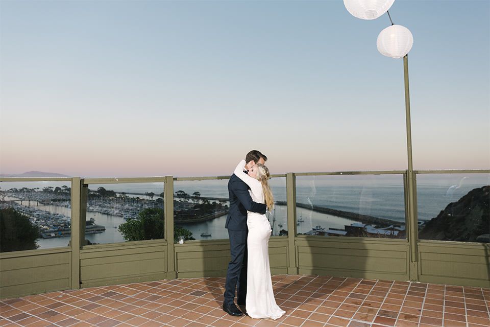 Dana point outdoor beach wedding at cannons seafood grill bride simple high neckline gown with long sleeves and a crystal belt with groom navy blue shawl lapel tuxedo with white dress shirt and black bow tie with white floral boutonniere first dance