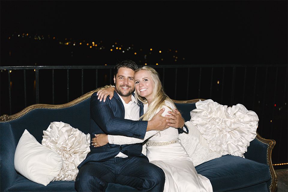 Dana point outdoor beach wedding at cannons seafood grill bride simple high neckline gown with long sleeves and a crystal belt with groom navy blue shawl lapel tuxedo with white dress shirt and black bow tie with white floral boutonniere sitting on couch and hugging