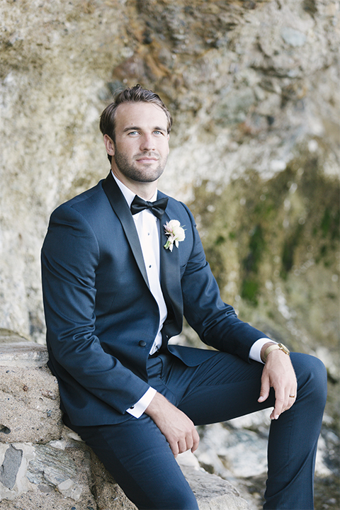 Dana point outdoor beach wedding at cannons seafood grill groom navy blue shawl lapel tuxedo with white dress shirt and black bow tie with white floral boutonniere sitting