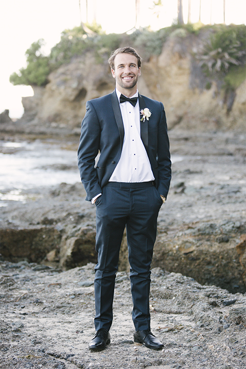 Dana point outdoor beach wedding at cannons seafood grill groom navy blue shawl lapel tuxedo with white dress shirt and black bow tie with white floral boutonniere standing with hands in pockets