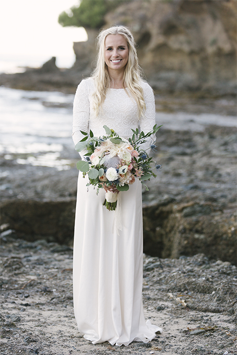 Dana point outdoor beach wedding at cannons seafood grill bride simple high neckline gown with long sleeves and a crystal belt holding white and green floral bridal bouquet