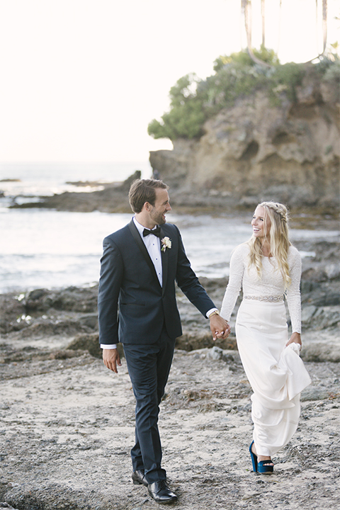 Dana point outdoor beach wedding at cannons seafood grill bride simple high neckline gown with long sleeves and a crystal belt with groom navy blue shawl lapel tuxedo with white dress shirt and black bow tie with white floral boutonniere walking on the beach and holding hands