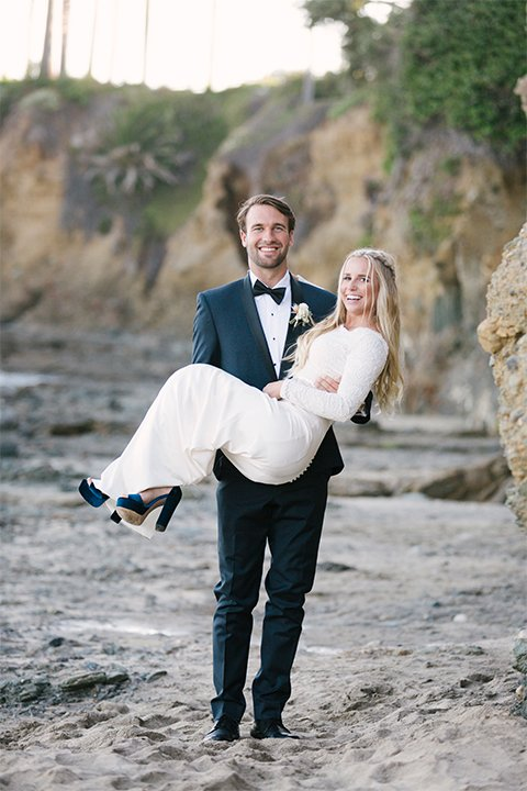 Dana point outdoor beach wedding at cannons seafood grill bride simple high neckline gown with long sleeves and a crystal belt with groom navy blue shawl lapel tuxedo with white dress shirt and black bow tie with white floral boutonniere groom carrying bride