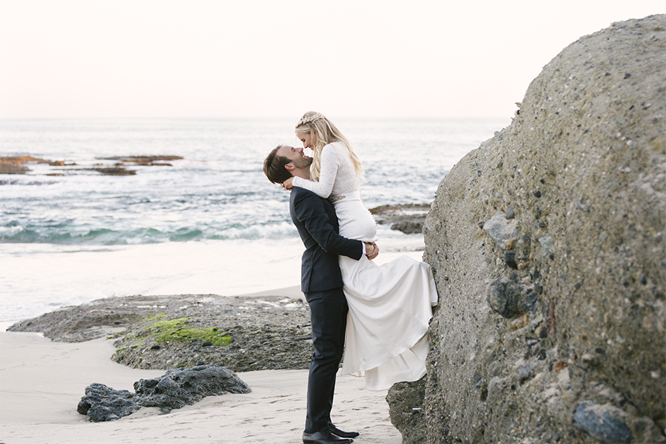 Dana point outdoor beach wedding at cannons seafood grill bride simple high neckline gown with long sleeves and a crystal belt with groom navy blue shawl lapel tuxedo with white dress shirt and black bow tie with white floral boutonniere groom hugging and lifting up bride on the beach