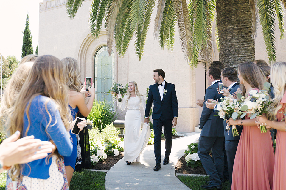 Dana point outdoor beach wedding at cannons seafood grill bride simple high neckline gown with long sleeves and a crystal belt with groom navy blue shawl lapel tuxedo with white dress shirt and black bow tie with white floral boutonniere walking and holding hands grand entrance