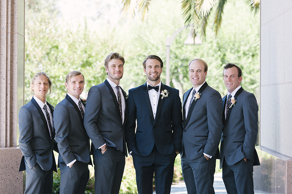 Dana point outdoor beach wedding at cannons seafood grill groom navy blue shawl lapel tuxedo with white dress shirt and black bow tie with white floral boutonniere standing with hands in pockets with groomsmen charcoal grey shawl lapel tuxedos with long grey ties